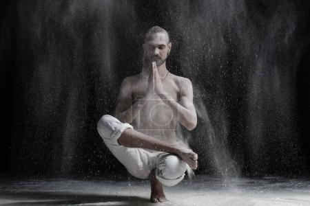 Young calm caucasian man doing yoga or pilates exercise. Sitting in squat position, Half Lotus Toe Balance
