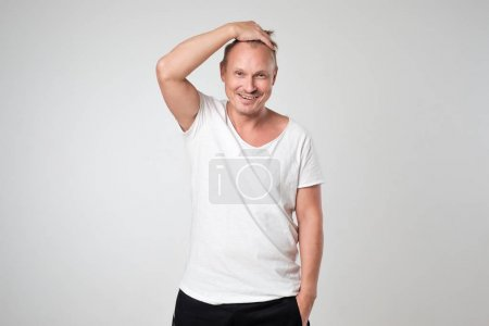 Smiling young man in white t-shirt standing against white background Concept of self confident man.