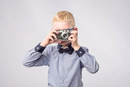 Cheerful smiling child boy holding a instant camera