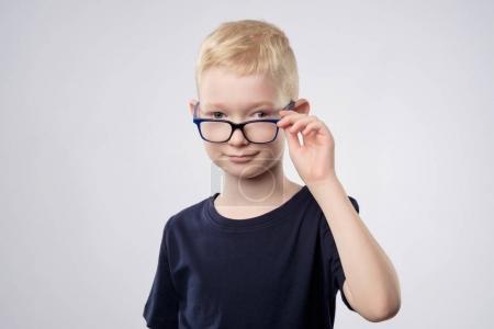 Cute caucasian blond boy holding glasses near eyes