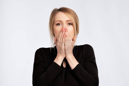 caucasian sad surprised excited woman in black dress covering with hands her mouth with blank copyspace.