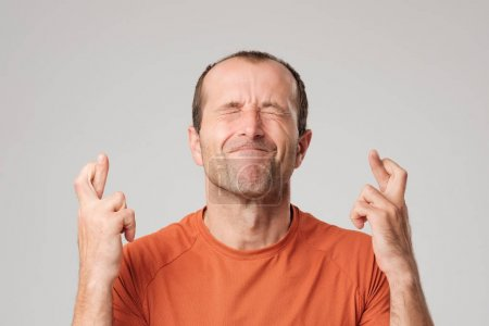Mature hispanic man making a wish sign with crossing fingers isolated on background.