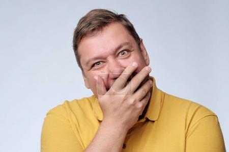 Mature fat man studio portrait. He closes his mouth with delight.