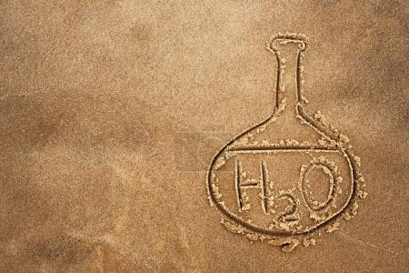Painted flask and chemical formula of water on sand. The quality of water on the beach and the ocean.
