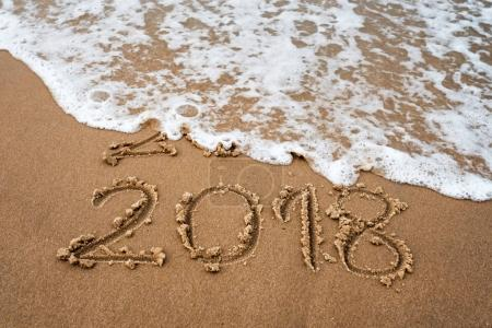 Concept of holidays. Happy New Year 2018 replace 2017 on the sea beach