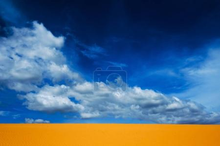 Bright yellow sand empties against the blue sky with clouds.