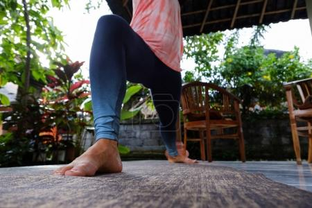 Photo for Young woman doing yoga asana Virabhadrasana Warrior Pose outside on terrace during vacation. Concept of your own practice - Royalty Free Image