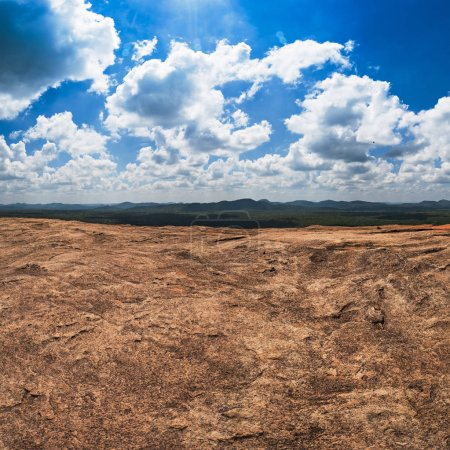 Massive rocks and view on blue cloudy sky and green forest