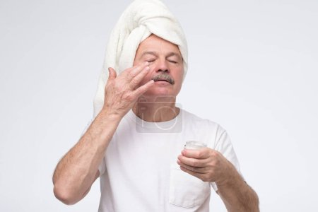 Photo for Handsome senior man in towel is applying anti aging cream to his face in the morning - Royalty Free Image