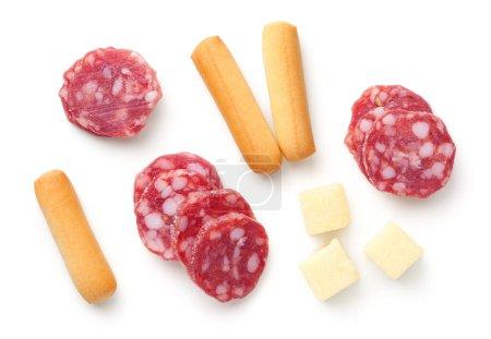Photo pour Tranches de salami, mini bâtonnets de pain grissini, morceaux de fromage à pâte dure isolés sur fond blanc. Amuse-gueule italien. Pose plate. Vue du dessus - image libre de droit