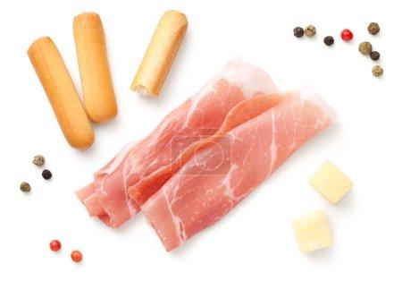 Photo pour Amuse-gueule italien, tranches de prosciutto, mini bâtonnets de pain grissini, morceaux de fromage à pâte dure isolés sur fond blanc. Vue de dessus, plan plat - image libre de droit