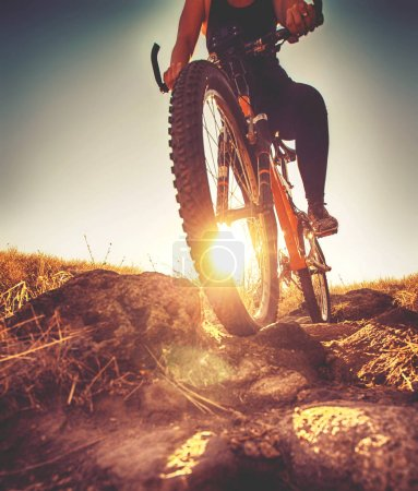 Woman riding a bicycle down a dirt trail