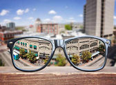 hipster glasses on a park bench with a cityscape