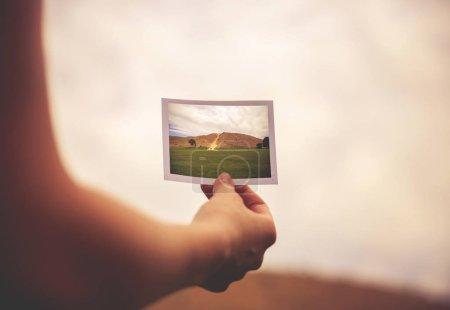 Photo pour Une femme tenant une photo instantanée d'une colline devant elle - concept de destination ou de persévérance teinté d'un filtre vintage rétro - image libre de droit
