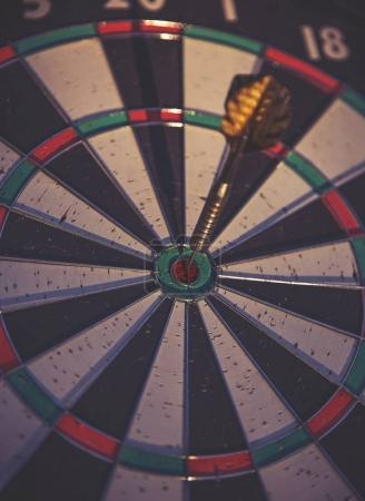 a dark moody image of a dartboard with a dart in the center bull