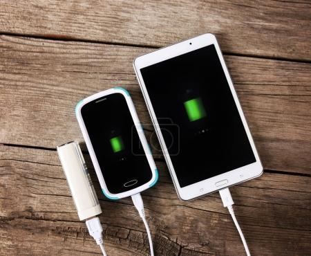 cell phone and a tablet on a vintage wooden background next to a portable charger with battery levels showing on the touch screens toned with a dark vintage retro instagram filter