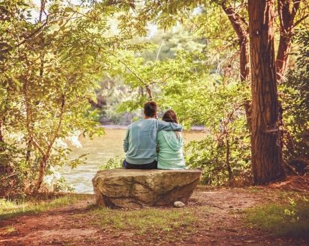 a couple in love sitting on a river bank with the man draping his arm over the woman on a warm summer day