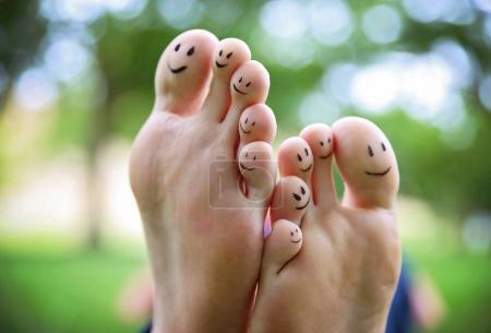 Photo pour Visages souriants sur une paire de pieds sur les dix orteils dans un parc par une chaude journée d'été - image libre de droit