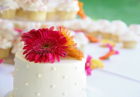 Photo for Authentic candid photo of a beautiful wedding cake and other pastries on a table before a reception toned with a warm retro vintage instagram filter - Royalty Free Image