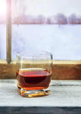 glass of whiskey or other alcohol in front of a cabin window on a cold winter day with trees and mountains in the view