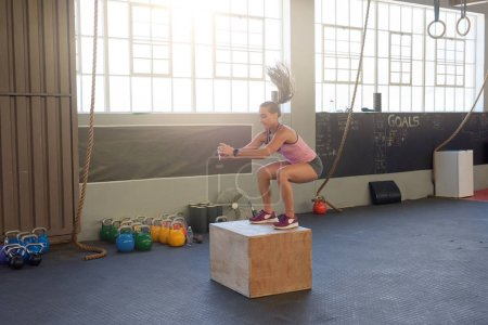 active woman doing box jumps