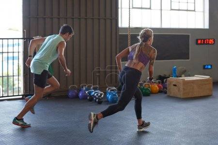 Photo for Sportive couple sprinting in gym for intense training session - Royalty Free Image