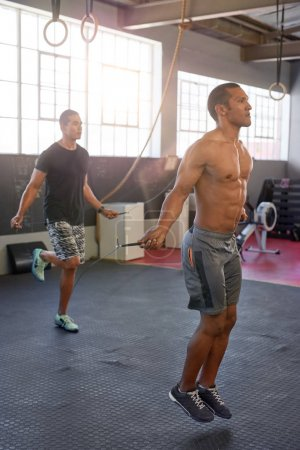 men jumping with skipping ropes in gym