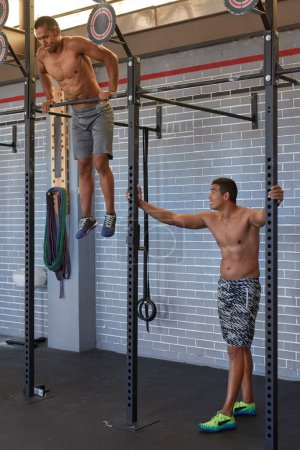 Shirtless men working out in gym