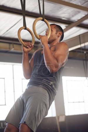 man hanging on gymnastic rings