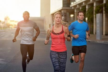 people jogging on road in city