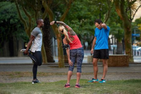 sportive people stretching in park