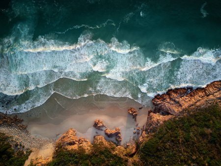 Photo for Beautiful ocean waves breaking on coastline, beach with rough rocky coastline, aerial photography overhead - Royalty Free Image
