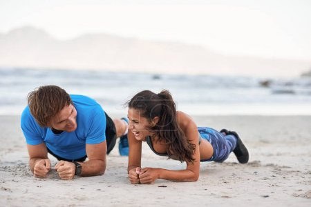 couple laughing while planking on sand