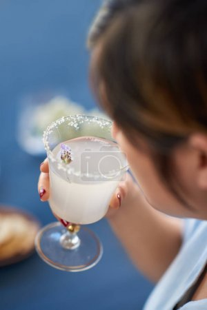 woman holding lemon lavendar cocktail with flower