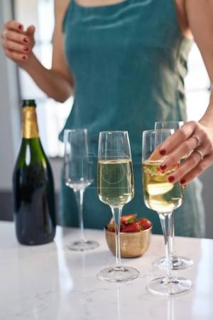 woman holding champagne glass with bubbles at table with bottle and bowl with strawberries