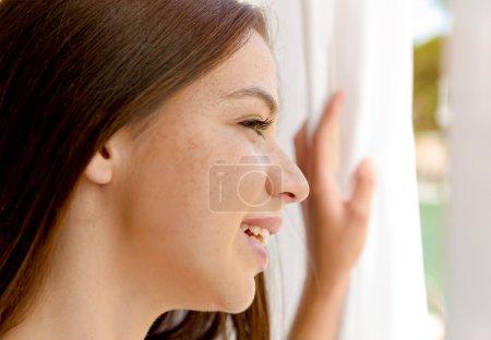 Photo pour Jolie femme à la recherche dans la fenêtre de la chambre d'hôtel - image libre de droit