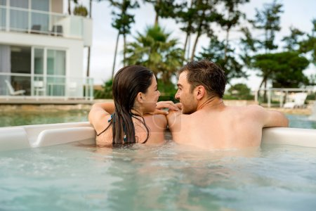 couple in jacuzzi looking each other