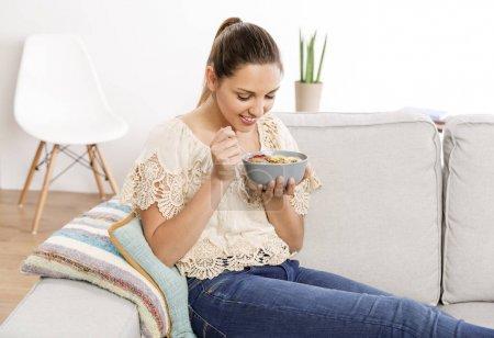 woman at home eating healthy bowl