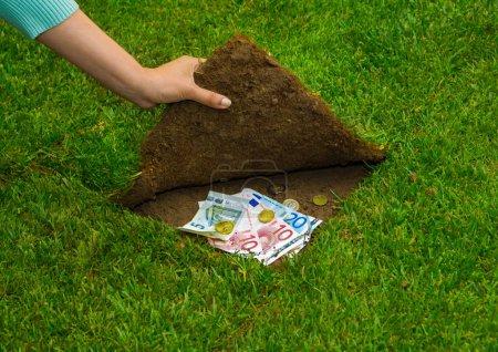hands hiding money under grass