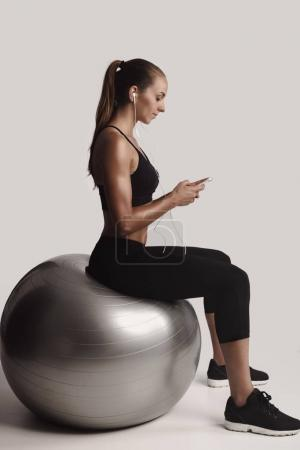 young woman sitting on fitball