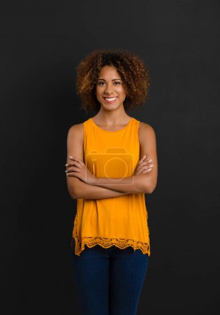 Photo for Beautiful African American woman in yellow dress standing with hands folded - Royalty Free Image
