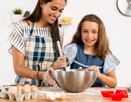Photo pour Famille s'amuser dans la cuisine et mère apprendre fille faire des gâteaux - image libre de droit