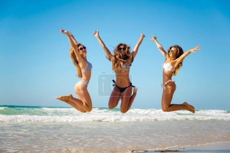 Photo for Beautiful teenage girls jumping on beach - Royalty Free Image