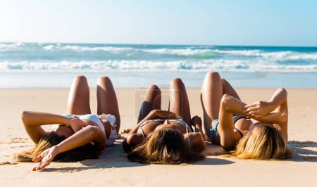 Beautiful girls lying on sand