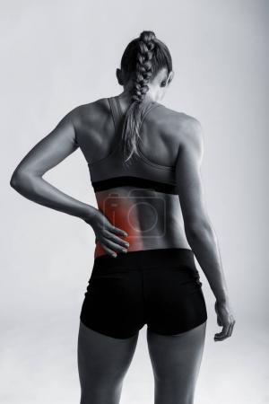Photo pour Plan studio d'une jeune femme sportive tenant son bas du dos dans la douleur - image libre de droit
