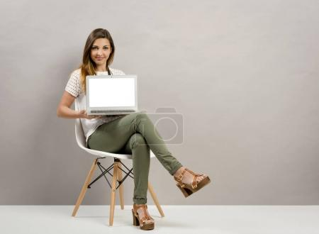 Photo for Beautiful woman sitting on a chair and showing something on a laptop - Royalty Free Image