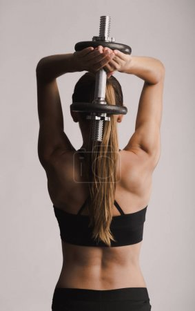 woman in a workout gear lifting dumbbell