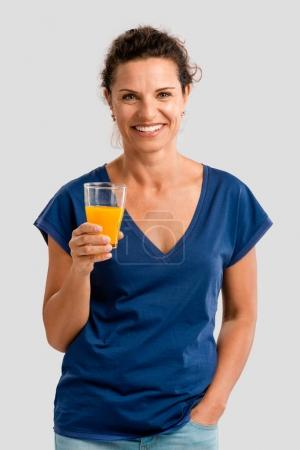 woman holding glass with orange juice