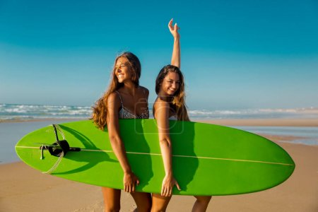 two women posing at camera on beach