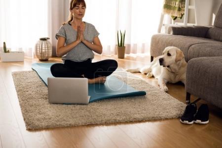 woman meditates with dog